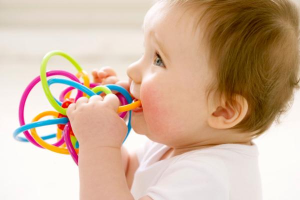 Малыш засовывает игрушку в рот