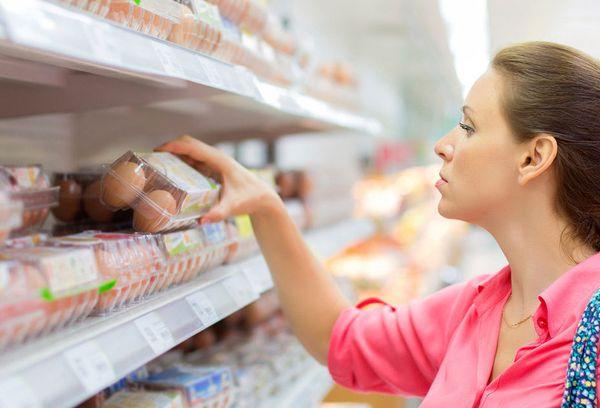 женщина выбирает яйца в магазине